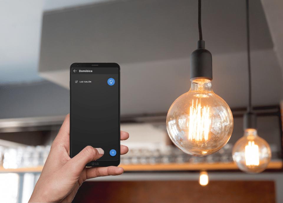 Móvil mostrando la pantalla de la app dómotica de Qvadis y encendiendo la luz de una bombilla a su derecha